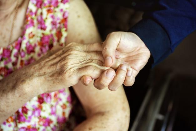 Close-up, handen van een bejaarde die de hand van een jongere vrouw houdt. medisch en gezondheidszorgconcept