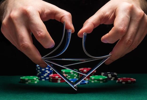 Close-up handen van een persoon-dealer of croupier die pokerkaarten schudt in een casino op de achtergrond van een tafel, chips