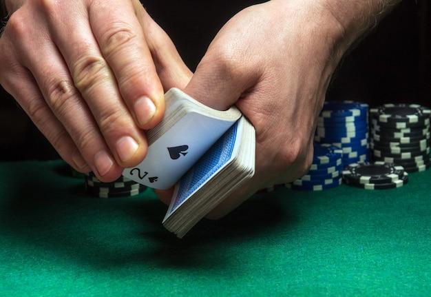 Close-up handen van een persoon-dealer of croupier die pokerkaarten schudt in een pokerclub op de achtergrond van een tafel, chips. pokerspel of gaming bedrijfsconcept