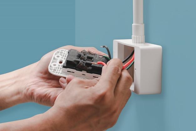 Close-up handen van elektricien sluit het netsnoer aan op het stopcontact