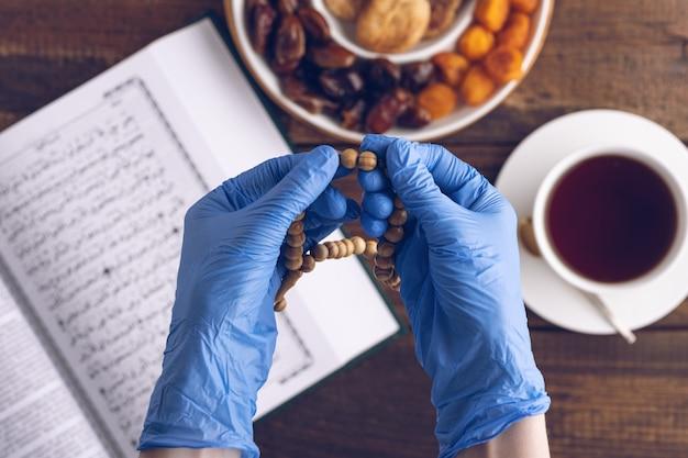 Close-up handen van gebed in blauwe medische handschoenen met houten rozenkrans op achtergrond van boek koran, kopje thee, bord met gedroogde vruchten, iftar concept, maand ramadan onder quarantaine, bovenaanzicht