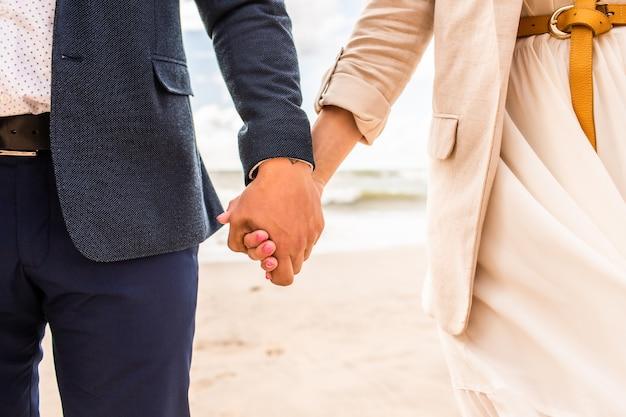 Close-up handen van gelukkig net getrouwd paar wandeling op het strand en veel plezier op zomerdag. gezichten zijn onherkenbaar.