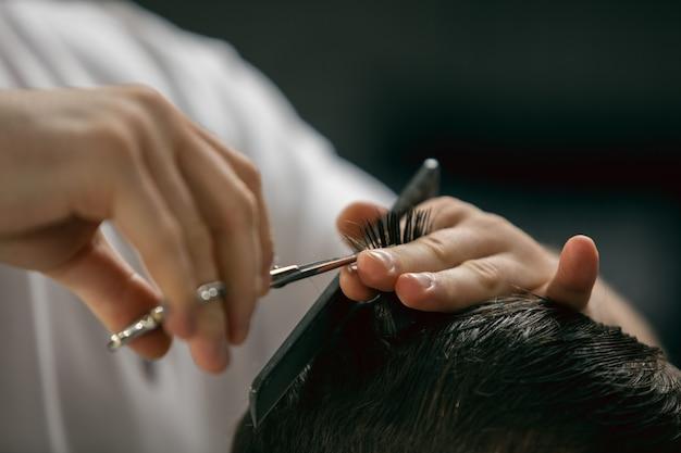 Close-up handen van meester kapper, stylist met sccissors doet het kapsel voor kerel, jonge man. professioneel beroep, mannelijk schoonheidsconcept. verzorgt het haar van de klant. zachte kleuren en focus, vintage.