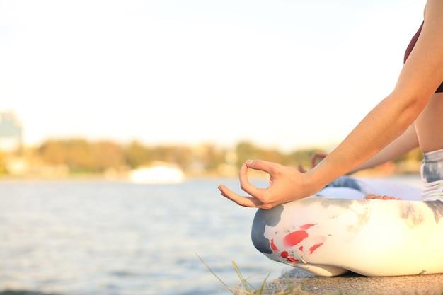 Close-up handen van vrouw doen yoga buiten, lotus pose. gezond en yogaconcept.