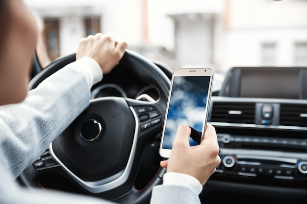 Close-up handen van vrouwelijke chauffeur in een auto zitten en het gebruik van mobiele telefoon.