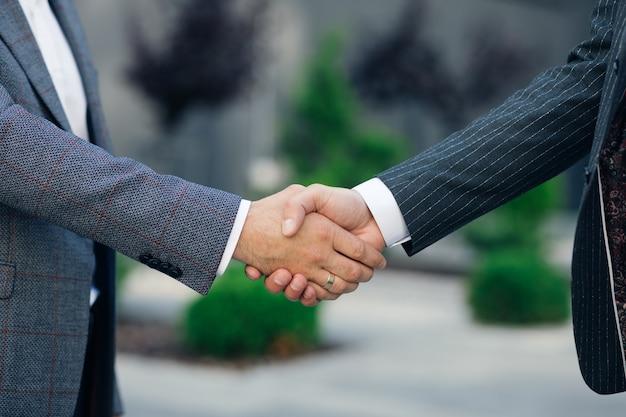 Close-up handen zakenmensen schudden succesvolle corporate partnership deal gastvrije gelegenheid bij business center achtergrondovereenkomst professionele begroeting meeting collega's partners.