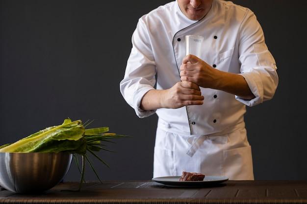 Close-up handen zout gieten op vlees