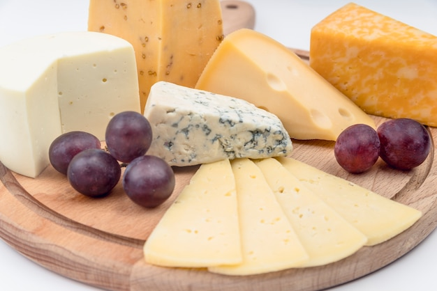 Close-up heerlijke verscheidenheid van kaas met druiven op de tafel