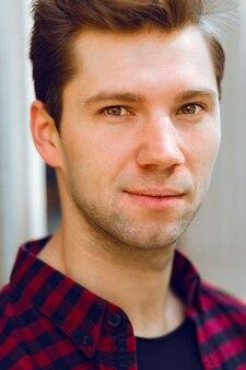 Close-up helder portret van jonge knappe hipster man, gekleed in geruite hemd, mooi gezicht, bruine ogen.