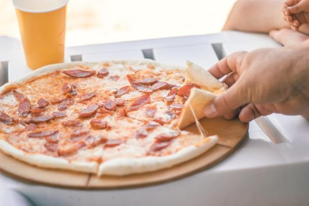 Close-up hele pizza met worstjes en kaas. strand eten.