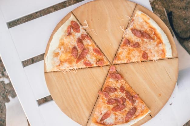 Close-up hele pizza met worstjes en kaas tekenvormige radioactiviteit bedorven strand eten concept