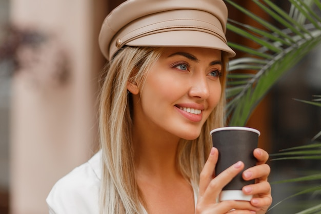 Close-up herfst portret van romantische blonde vrouw genieten van warme koffie buiten