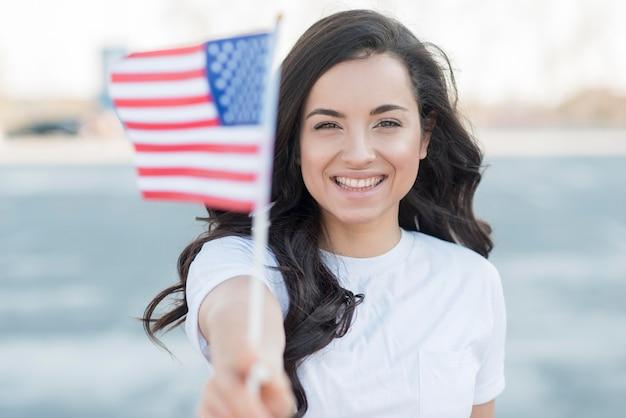 Close-up het donkerbruine de vlag van de vs van de vrouwenholding glimlachen
