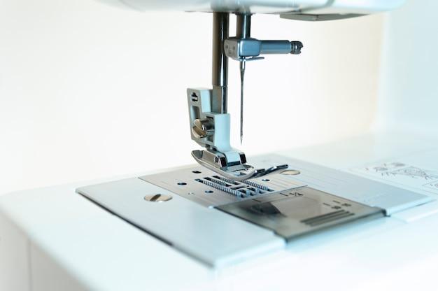Close-up: het mechanisme van de naaimachine. witte achtergrond.