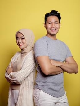 Close-up hijab vrouw en man glimlachend gekruiste armen kijken camera geïsoleerd op een gele achtergrond
