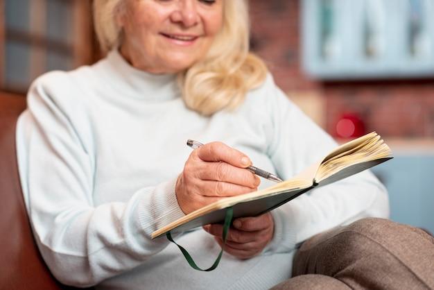 Close-up hogere vrouw die in agenda schrijven