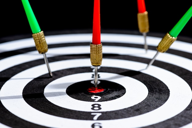 Close-up hoofd van dart pijlen raken target center dartbord op zwarte ondergrond