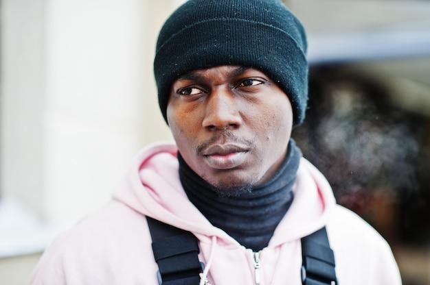 Close-up hoofd van stijlvolle stedelijke stijl afro-amerikaanse man in roze hoodie en zwarte hoed gesteld. bevroren adem.