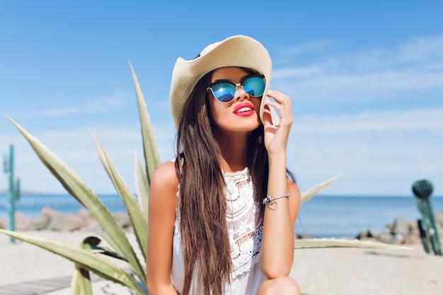 Close-up horizontaal portret van aantrekkelijke brunette meisje met lang haar, zittend op het strand in de buurt van cactus op de achtergrond. ze glimlacht ver weg.
