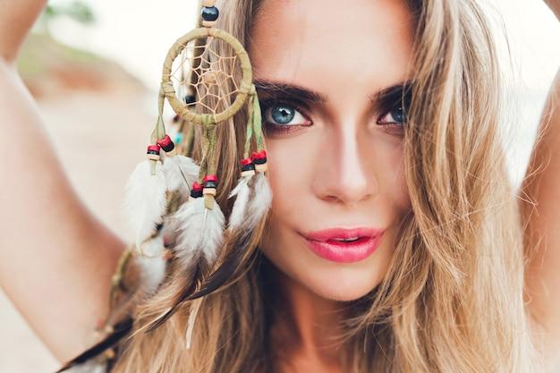 Close-up horizontaal portret van vrij blond meisje met lang haar op strand. ze houdt versieringen met veren in de hand en kijkt naar de camera.