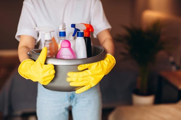 Close-up huishoudster in gele handschoen houdt teen vol wasmiddelen thuis
