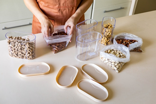 Close-up huisvrouw handen plaatsen noten plastic pakket in container doos op houten tafel in de keuken