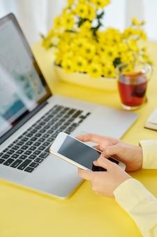 Close-up iamge van zakenvrouw zittend op kantoor deak en met behulp van mobiele applicatie op smartphone