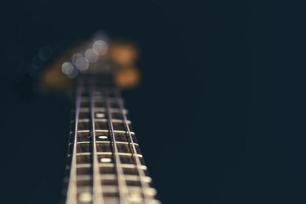 Close-up in focus van snaren op een basgitaar op een wazige zwarte achtergrond.