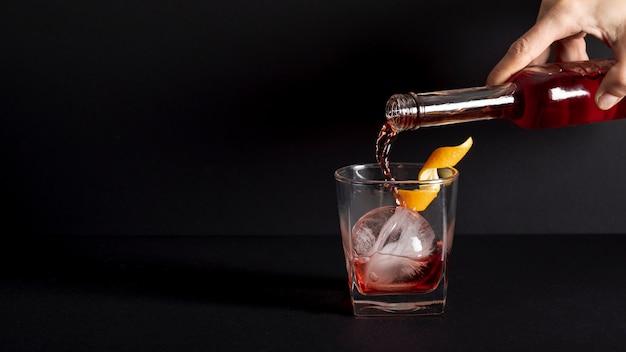 Close-up individuele gieten alcoholische drank in glas
