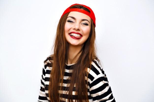 Close-up indoor fashion lifestyle portret van coole mooie jonge brunette vrouw, geweldige lange haren, lichte make-up, rode hoed en gestreepte t-shirt, geweldige grote glimlach, schattig gezicht, stedelijk imago met flits.