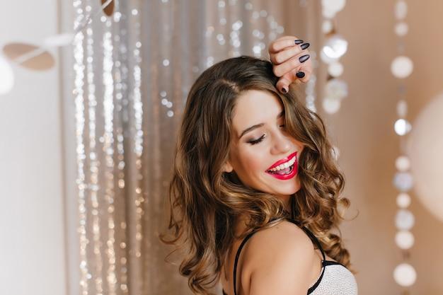 Close-up indoor foto van verfijnde europese vrouw met stijlvolle make-up ontspannen op verjaardagsfeestje. portret van huiveringwekkend krullend meisje met donker haar poseren in de buurt van sparkle decoratie.