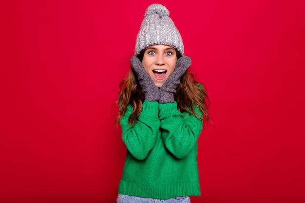 Close-up indoor portret van effectieve stijlvolle mooie vrouw met lang haar gekleed winter glb en groene trui met verrast emoties op geïsoleerde rode achtergrond