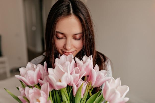 Close-up indoor portret van gelukkige vrouw met donker haar poseren met gesloten ogen en gelukkige glimlach met bloemen.