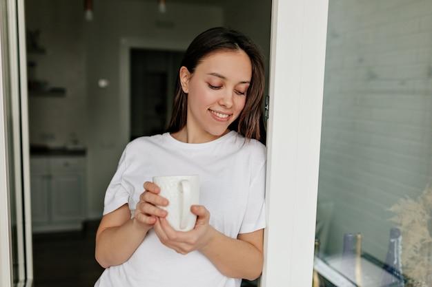 Close-up indoor portret van lachende europese vrouw met donker haar, gekleed in een wit t-shirt koffie drinken in de ochtend in de keuken.