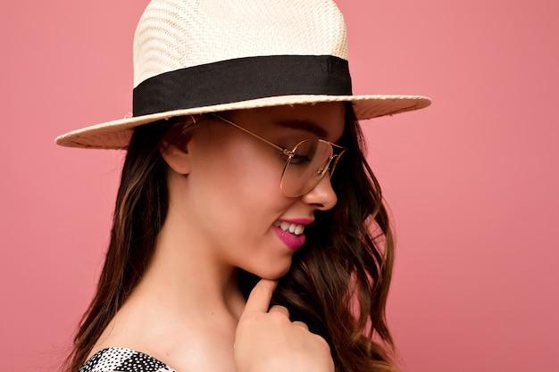 Close-up indoor portret van mooie vrouw met donker haar hoed dragen