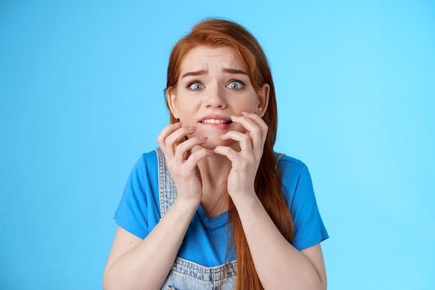 Close-up intens in paniek rakende roodharige vrouw die naar enge film kijkt voelt zich onder druk gezet, bijt op lip bezorgd, houdt handen in de buurt van mond zelfverzachtend probeert te kalmeren, staren camera angstig, blauwe achtergrond