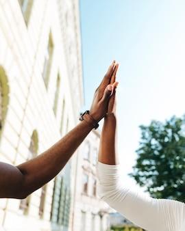 Close-up interculturele high five in de lucht