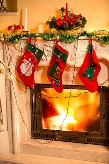 Close-up interieurfoto van drie kerstsokken die aan een versierde open haard hangen