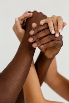 Close-up interraciale handen die elkaar vasthouden