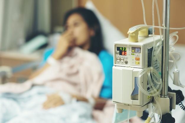 Close-up iv-machine terwijl en wazig van geduldige vrouw liggend slapen met lijden aan symptoom