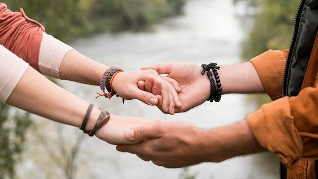 Close-up jong koppel hand in hand in de buurt van de rivier