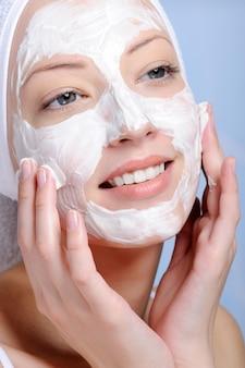 Close-up jong vrouwelijk gezicht in kosmetisch masker gekleurde achtergrond