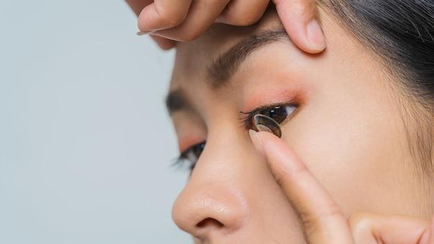 Close-up jonge aziatische vrouw die contactlens, macroschot draagt.