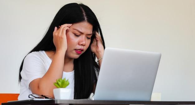 Close-up jonge aziatische vrouw stress met werkende baan op laptop bureau, millennial serieus en burn-out concept