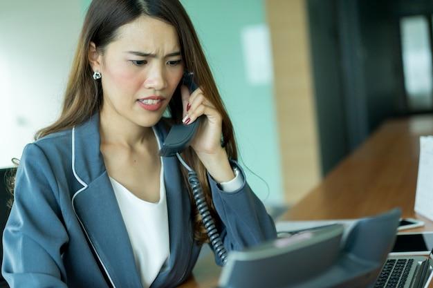 Close-up jonge aziatische zakenvrouw fronste op gezicht na het praten telefoon op kantoor werkplek
