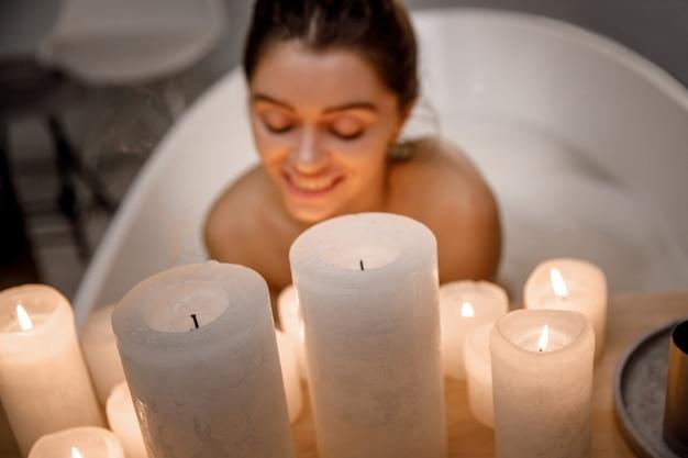 Close-up jonge en rustige vrouw ontspannen in het prachtige vintage bad vol schuim in de retro badkamer, versierd met kaarsen. gezonde behandeling en plezier.