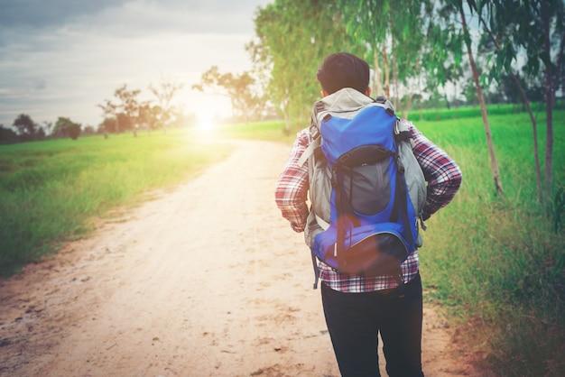 Close-up jonge hipster man met een rugzak op zijn schouder lopen