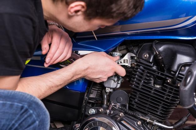 Close-up jonge man bezig met sommige delen van zijn blauwe motor met behulp van een moersleutel handgereedschap