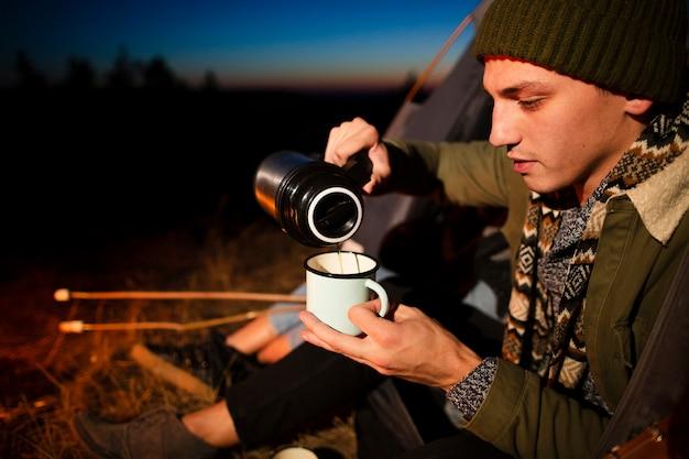 Close-up jonge man die een warme drank giet