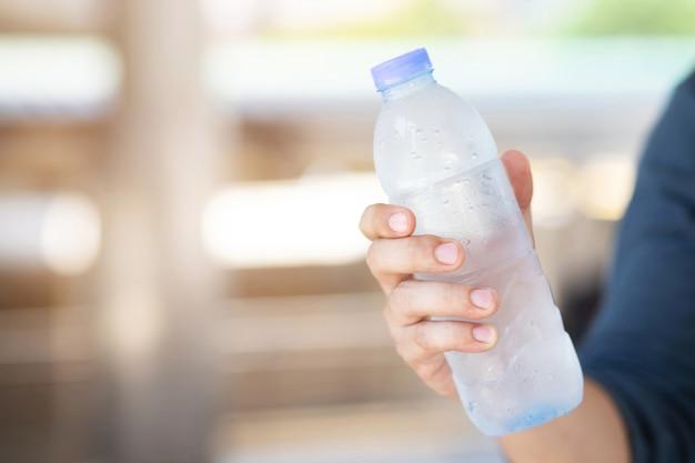 Close-up jonge man hand met vers drinken koud water fles uit een plastic in de buitenlucht.